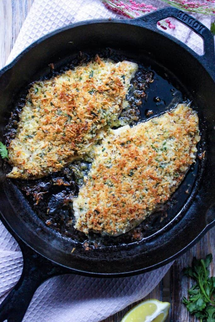 overhead shot of parmesan crusted catfish in cast iron skillet