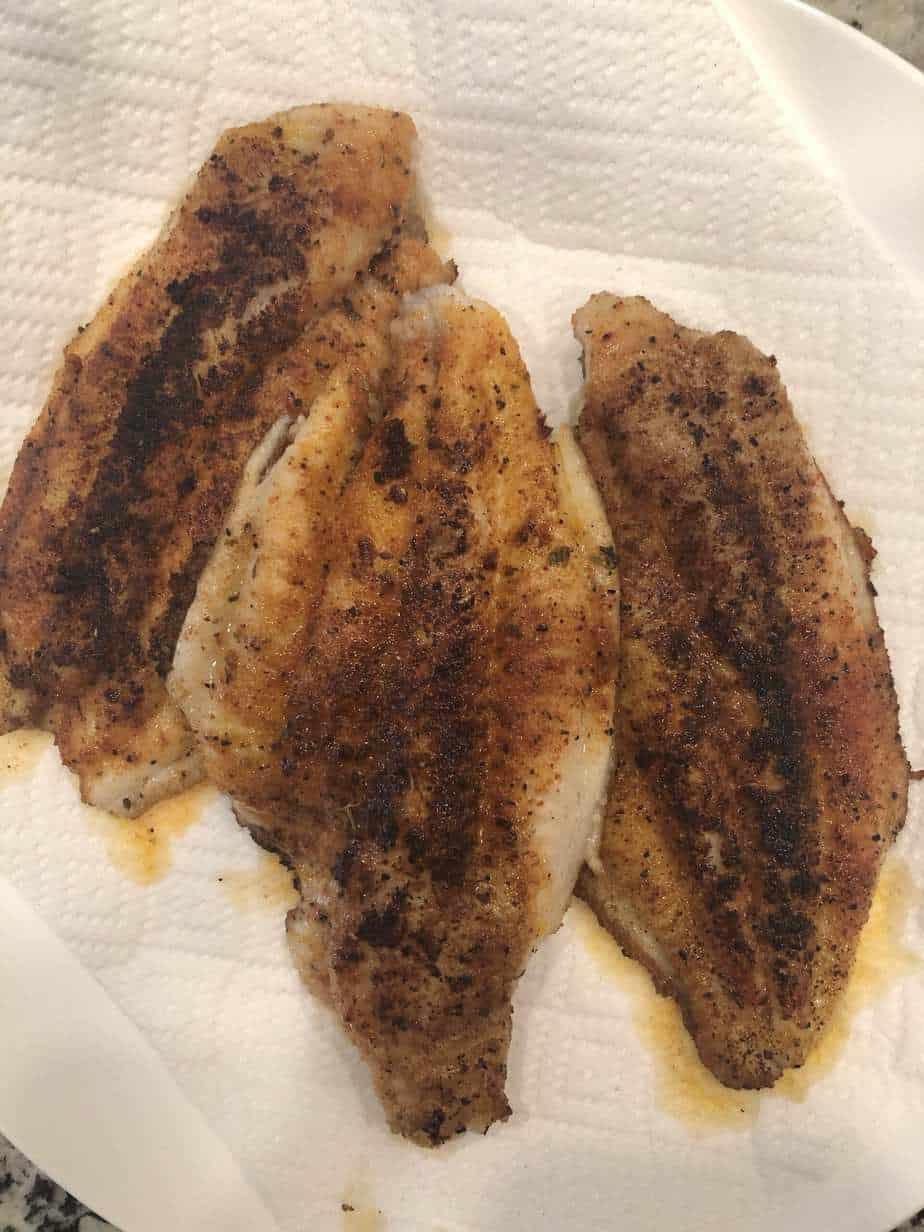 blacked catfish fillets on a paper towel lined plate.