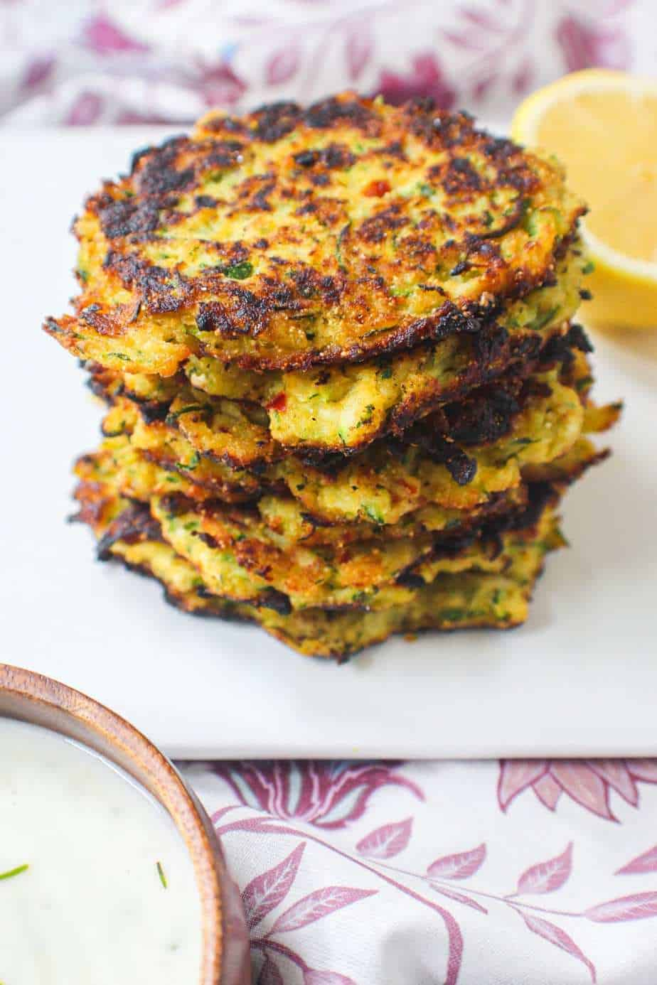side shot of a stack of cornmeal zucchini fritters on a white plate with a floral napkin underneath.