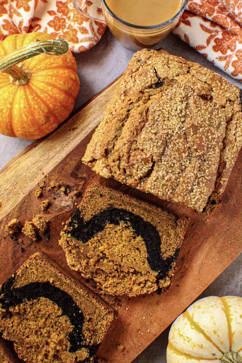 overhead shot of chocolate marble pumpkin bread on wooden board with orange floral towel and pumpkins in shot perimeter