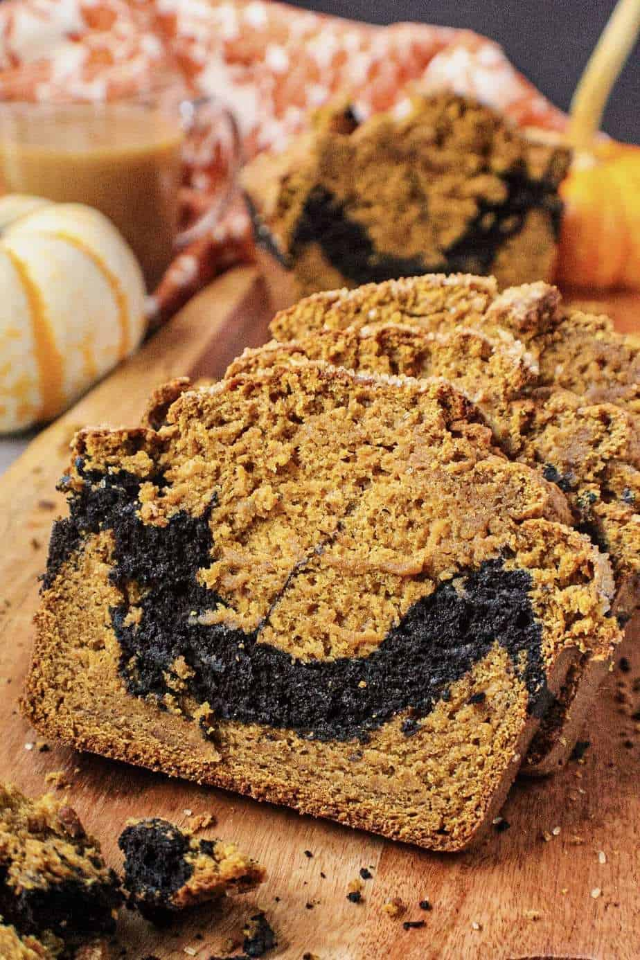 side shot of chocolate marble pumpkin bread on wooden board with orange floral towel and pumpkins in shot perimeter