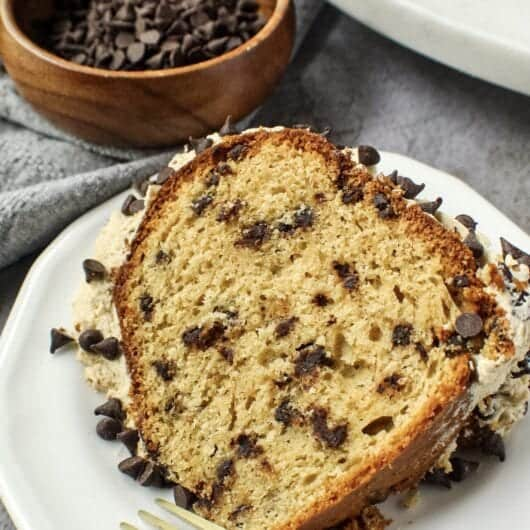 chocolate chip pound cake with cookie dough frosting on a small white plate.