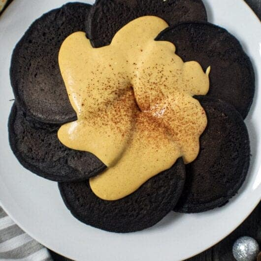 overhead shot of dark chocolate pancakes with pumpkin cream cheese glaze on white plate sitting on wooden surface