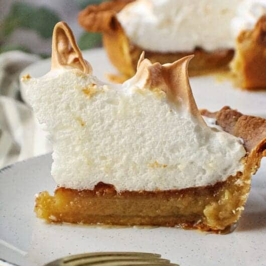 slice of maple chess pie topped with meringue peaks on white dessert plate