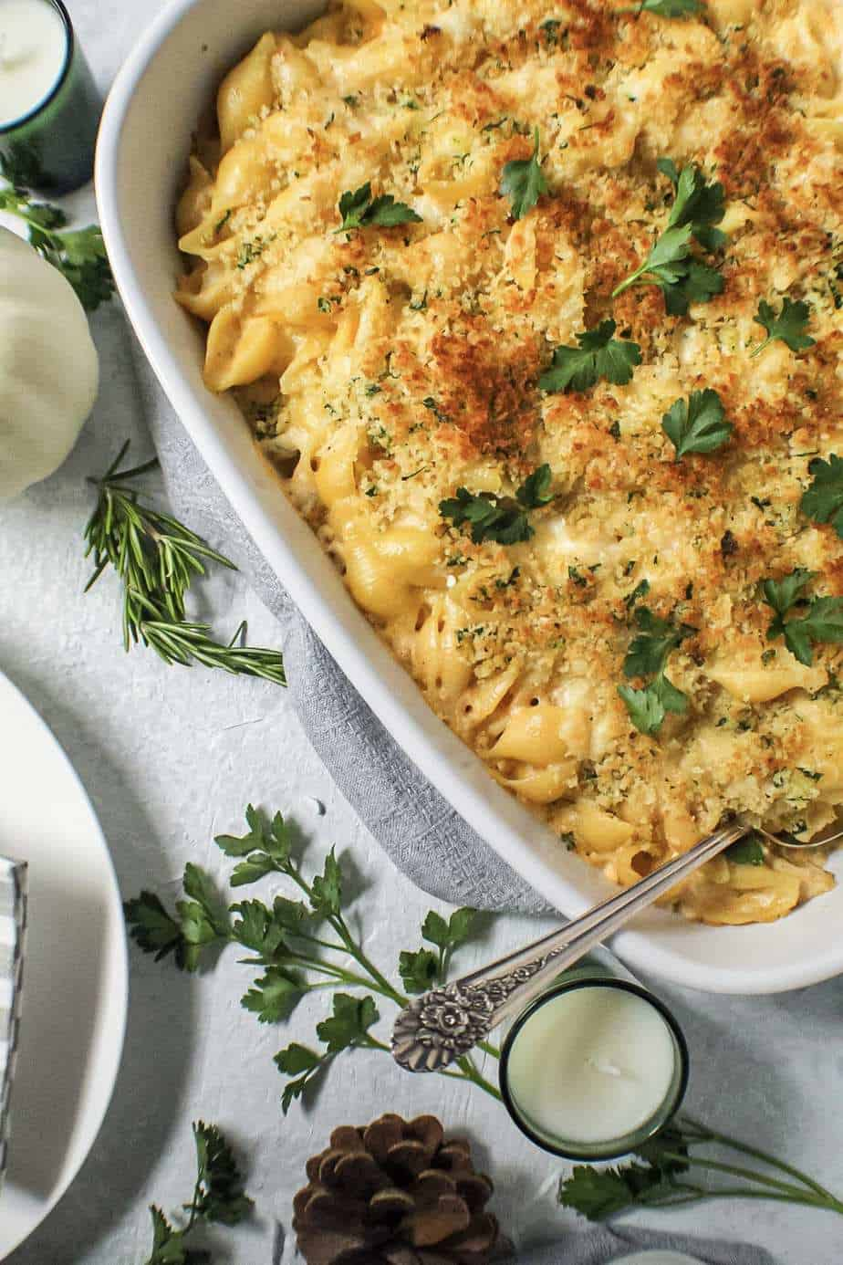 close up shot of smoked gouda mac and cheese in white casserole dish topped with fresh herbs