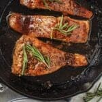 maple Dijon salmon in cast iron skillet topped with fresh rosemary. two plates and forks in corner