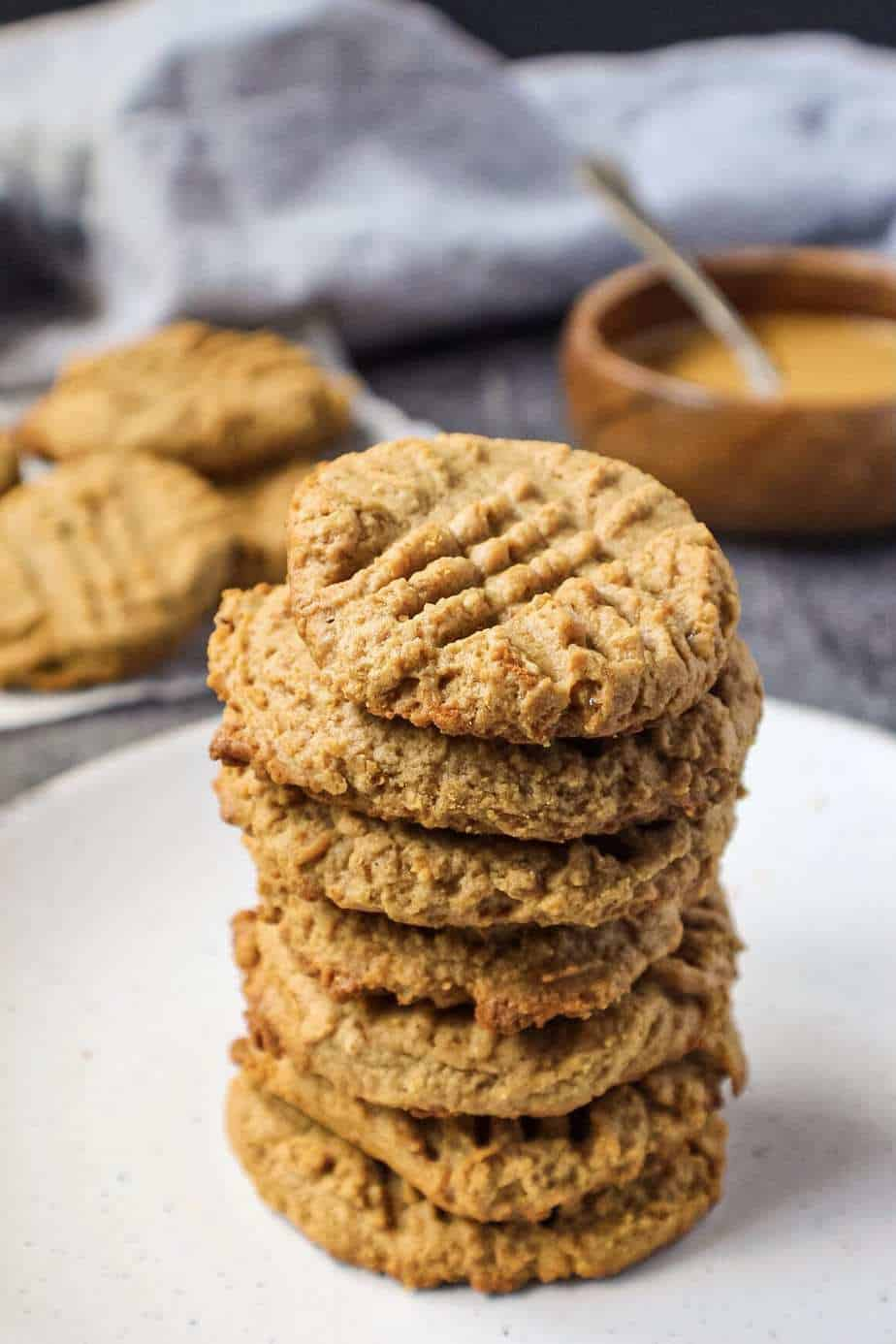 side shot of peanut butter cookies in a stack on white plate with bowl of peanut butter in background