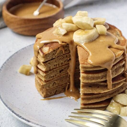 peanut butter banana pancakes in a stack with a section cut out topped with peanut butter drizzle and sliced bananas. bowl of peanut butter in background