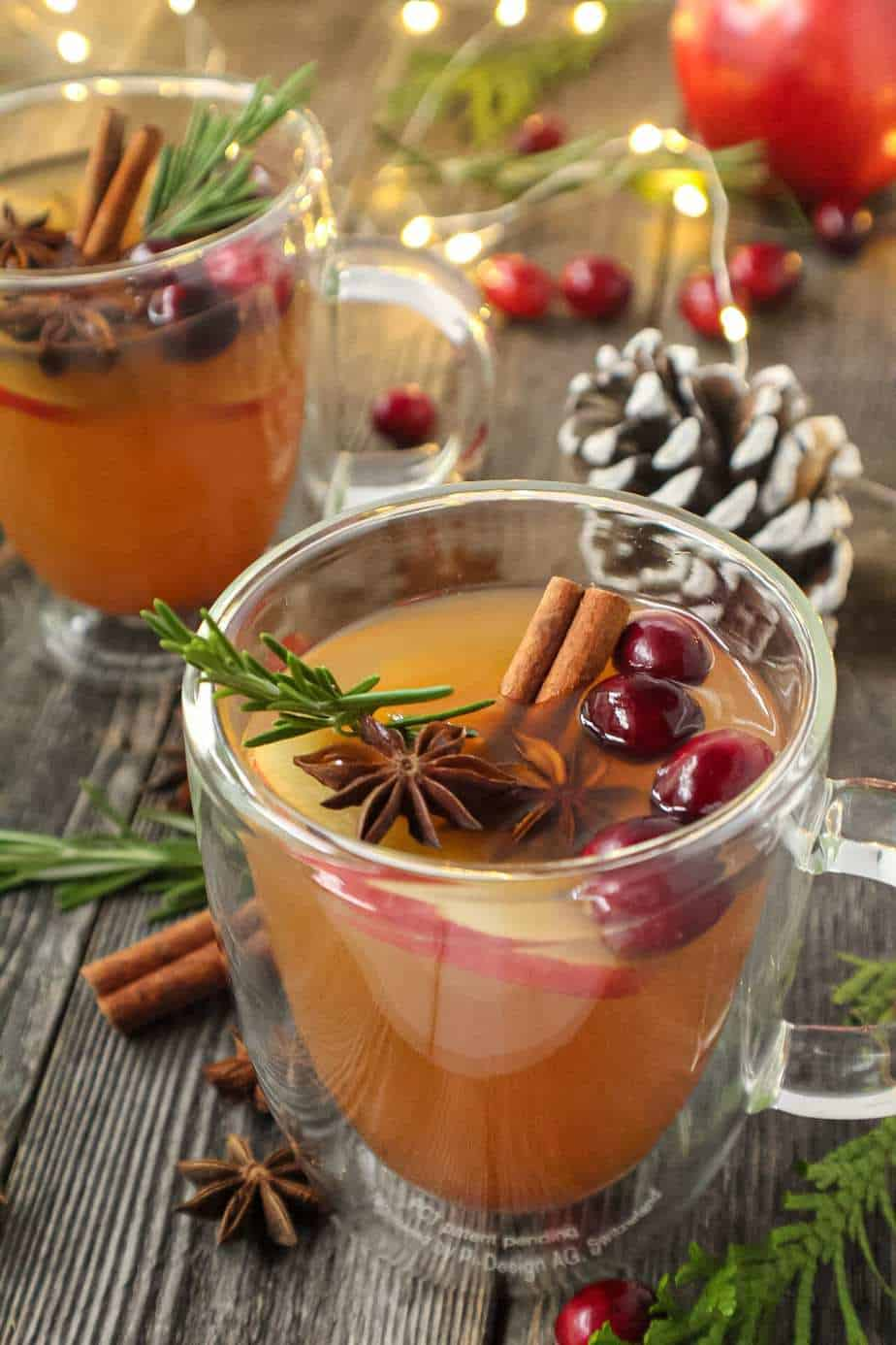 mulled apple cider served in clear mugs garnished with cinnamon sticks, star anise and cranberries on top of wooden surface