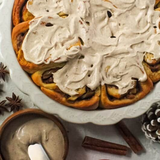 apple cinnamon rolls with chai cream cheese frosting on top in white pie dish with one cinnamon roll on a blue and white plate next to pie dish with cinnamon sticks and star anise in shot.
