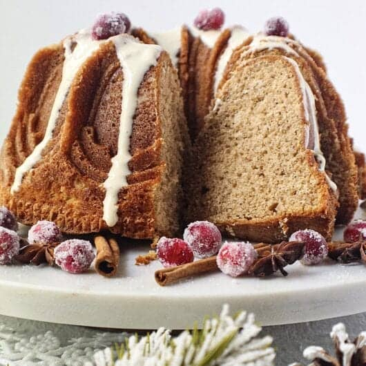 chai spice cake with maple cream cheese glaze on white serving plate with sugared cranberries on top and cinnamon sticks and star anise arranged around cake
