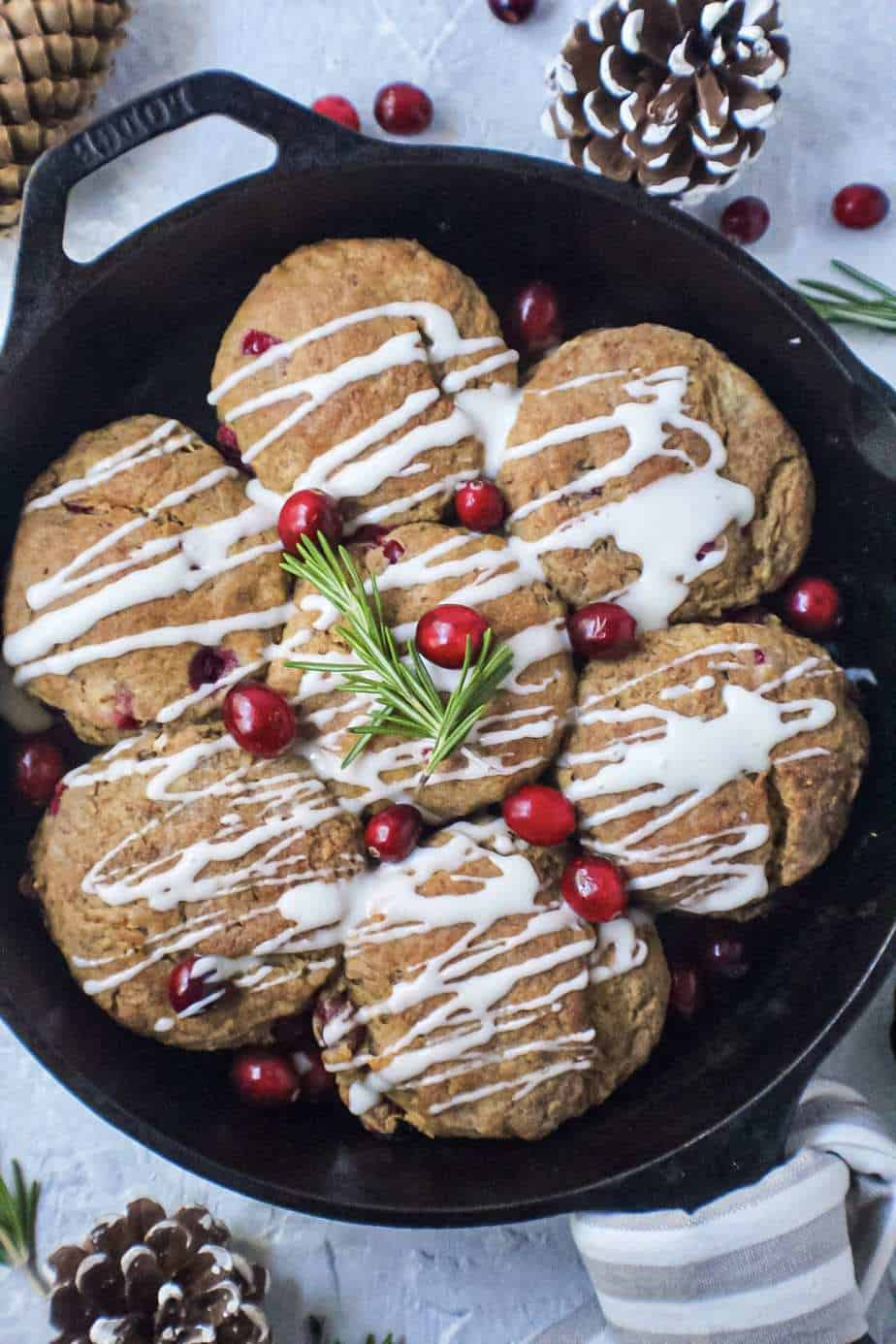 cranberry buttermilk biscuits topped with powdered sugar glaze in cast iron skillet garnished with fresh cranberries