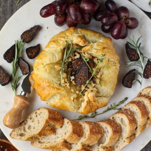 brie cheese wrapped in puffed pastry and baked until golden served on white platter with grapes, figs and bread slices around baked brie.