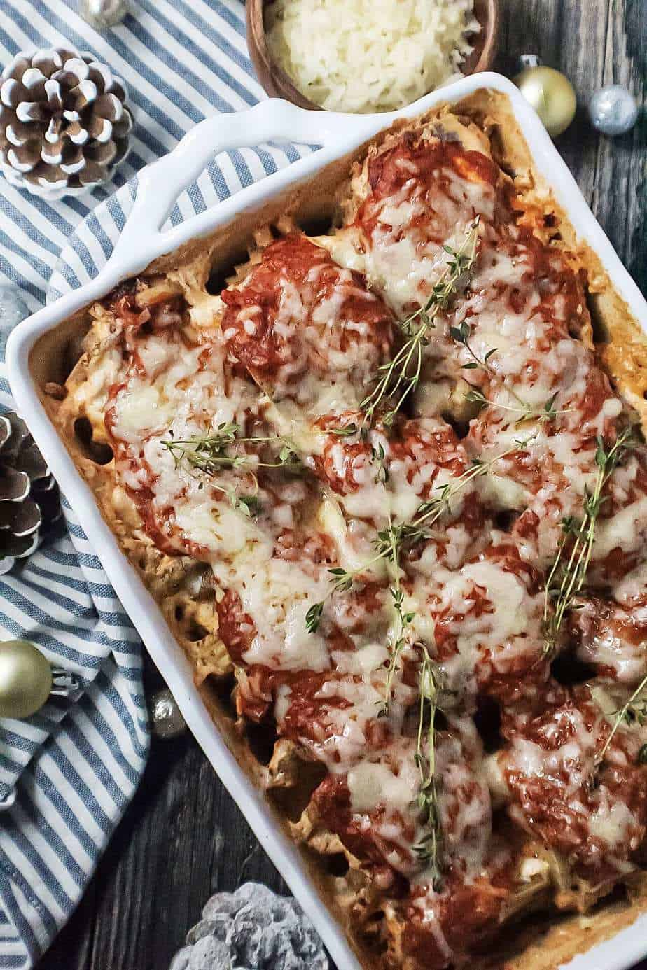 sliced potatoes topped with red pesto and cheese in a white baking dish garnished with fresh herbs and on top of striped linen.