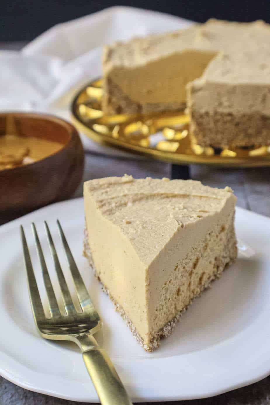vegan peanut butter cheesecake on gold trivet with a slice of cheesecake on a small white plate with fork