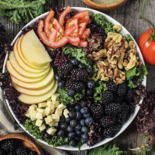 overhead shot of apple berry walnut salad with leaf lettuce, kale, sliced apples, walnuts, tomatoes, berries and cheese cubes in a large white bowl on wood surface with salad dressing in a bowl and lettuce leaves around salad.