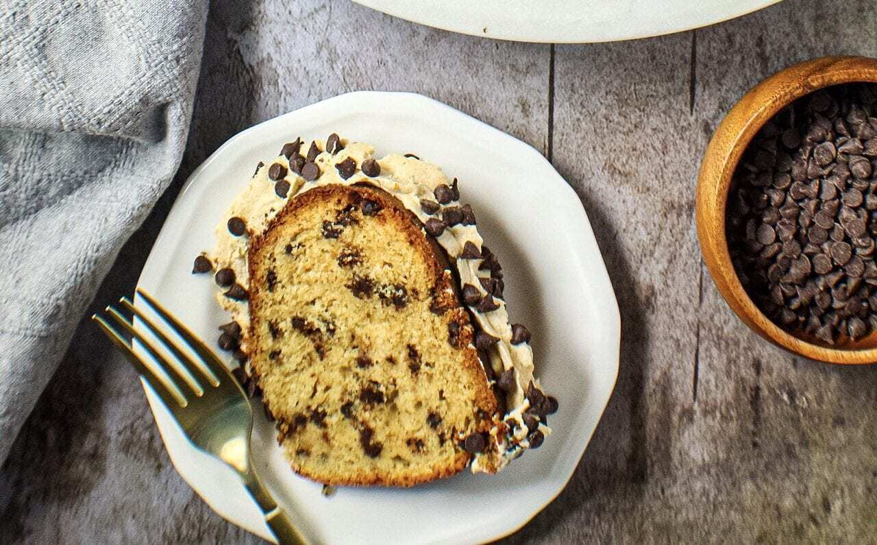 chocolate chip pound cake with cookie dough frosting slice on a small white plate with fork.