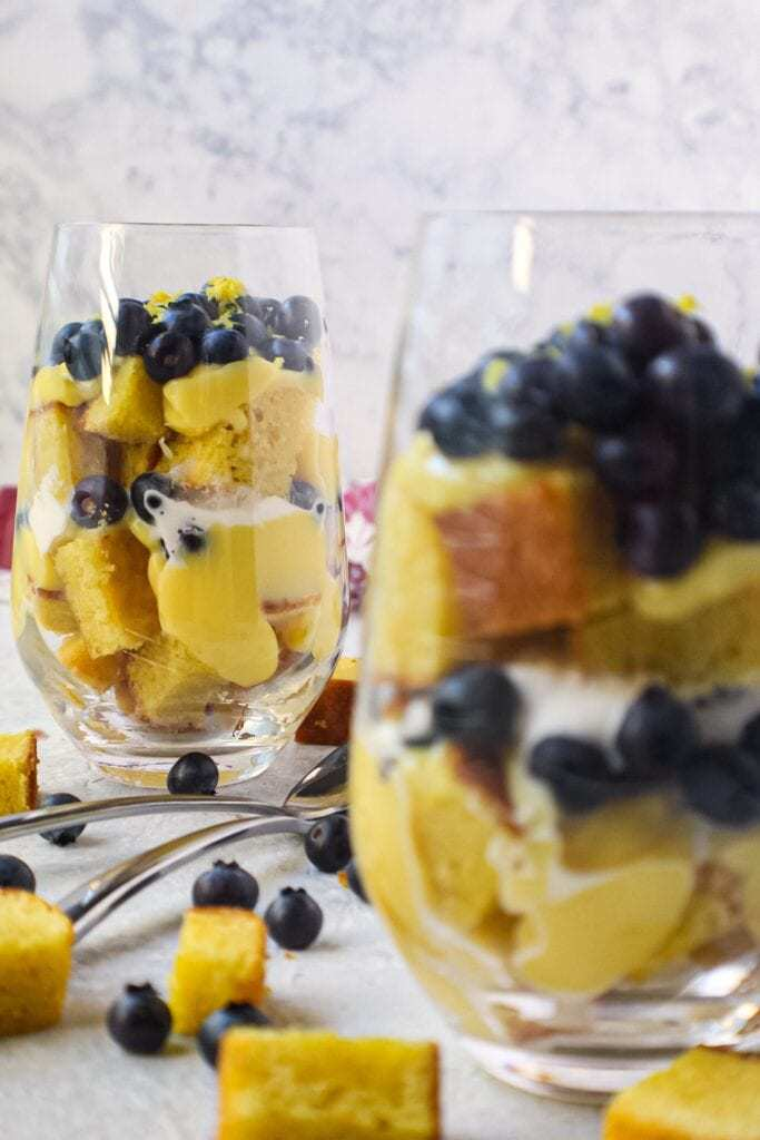side shot of lemon blueberry trifles served in wine glasses with cake pieces scattered on surface and colorful linen in background