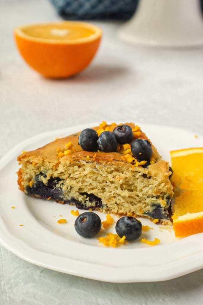 orange blueberry breakfast cake slice on small white plate with fresh blueberries on top and garnished with fresh orange slices and orange zest. Half an orange and blue towel in the background.