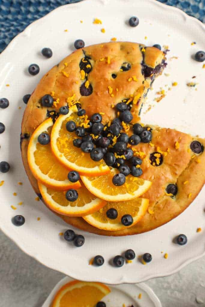 orange blueberry breakfast cake on white cake stand with fresh blueberries on top and garnished with fresh orange slices and orange zest. Half an orange and blue towel in the background.