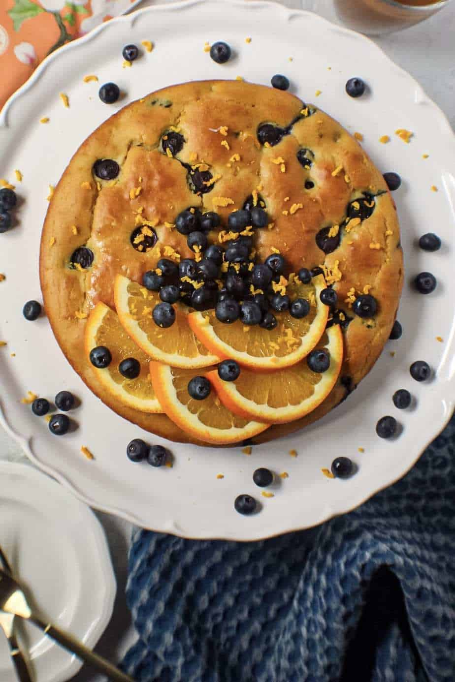 overhead shot of orange blueberry breakfast cake on white cake stand with fresh blueberries on top and garnished with fresh orange slices and orange zest. Half an orange and blue towel in the background.y breakfast cake