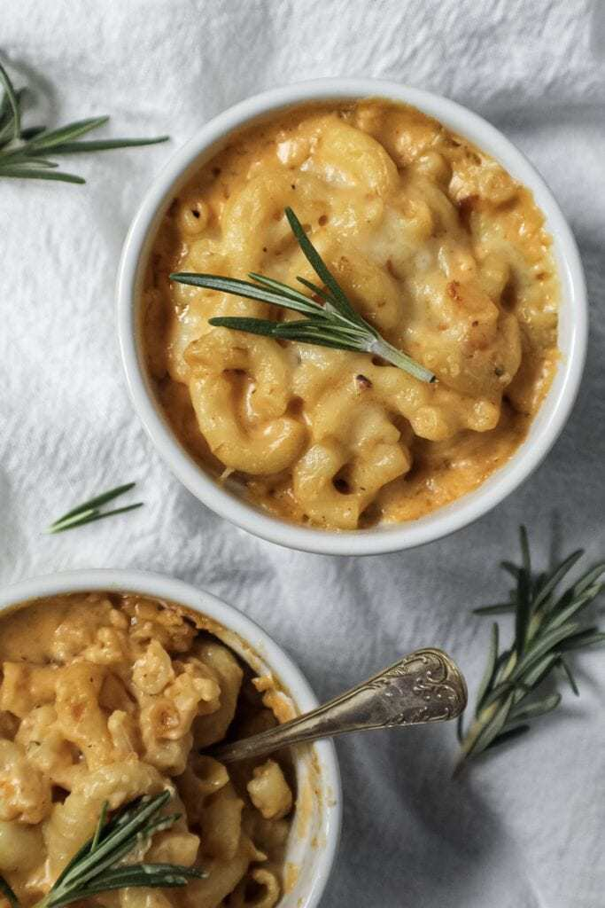 smoked cheddar mac and cheese served in two single-serve ramekins sitting on top of white linen topped with fresh rosemary and a small spoon inside one ramekin.