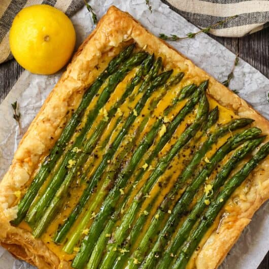overhead shot of asparagus tart on parchment sitting on a wood surface with a striped linen and half a lemon in perimeter of shot.