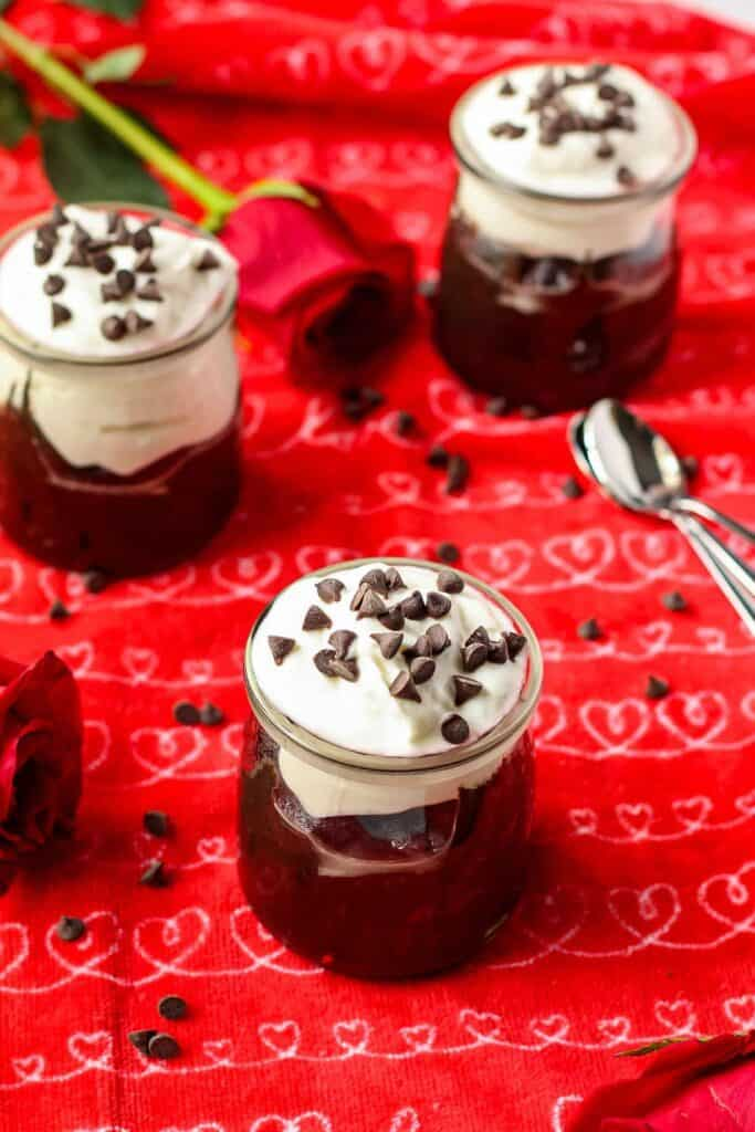 Dark chocolate avocado mousse in a yogurt jar topped with dairy-free yogurt and mini chocolate chips. Jars are on top of a red kitchen towel.