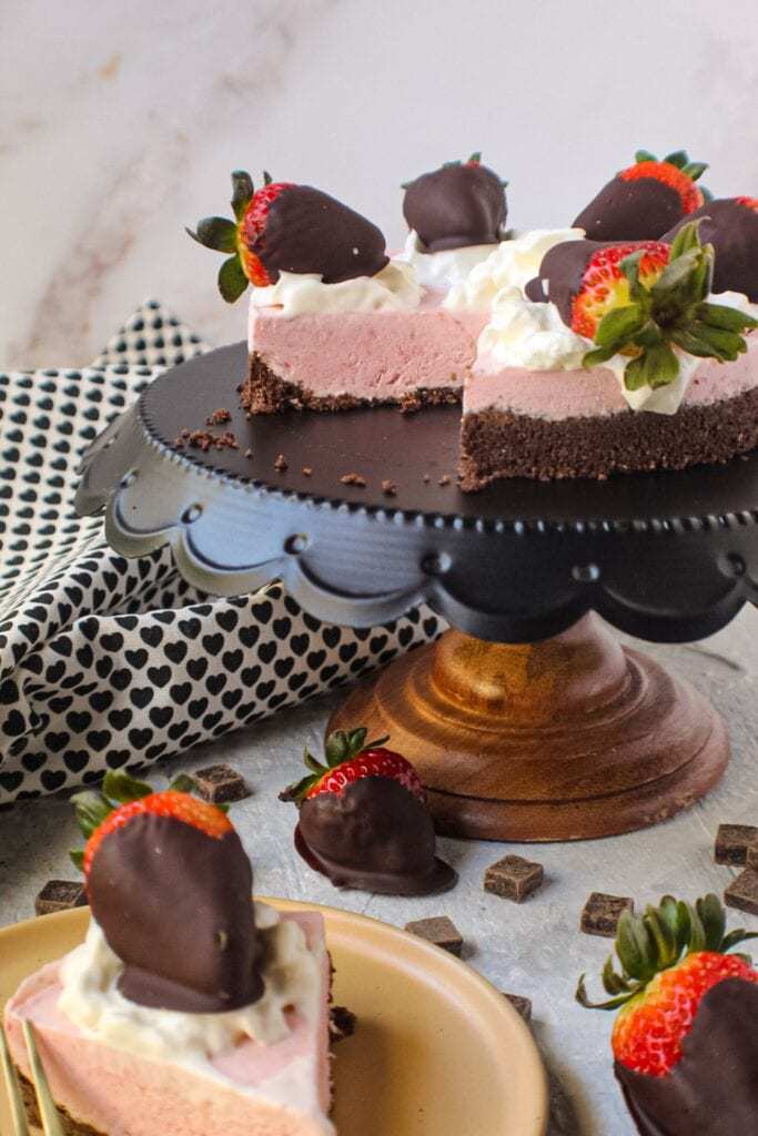 chocolate strawberry no-bake cheesecake on cake stand topped with whipped cream and strawberries