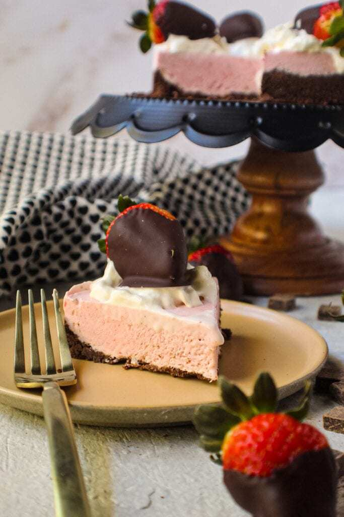 chocolate strawberry no-bake cheesecake slice on tan plate with whole cheesecake on cake stand in background topped with whipped cream and strawberries