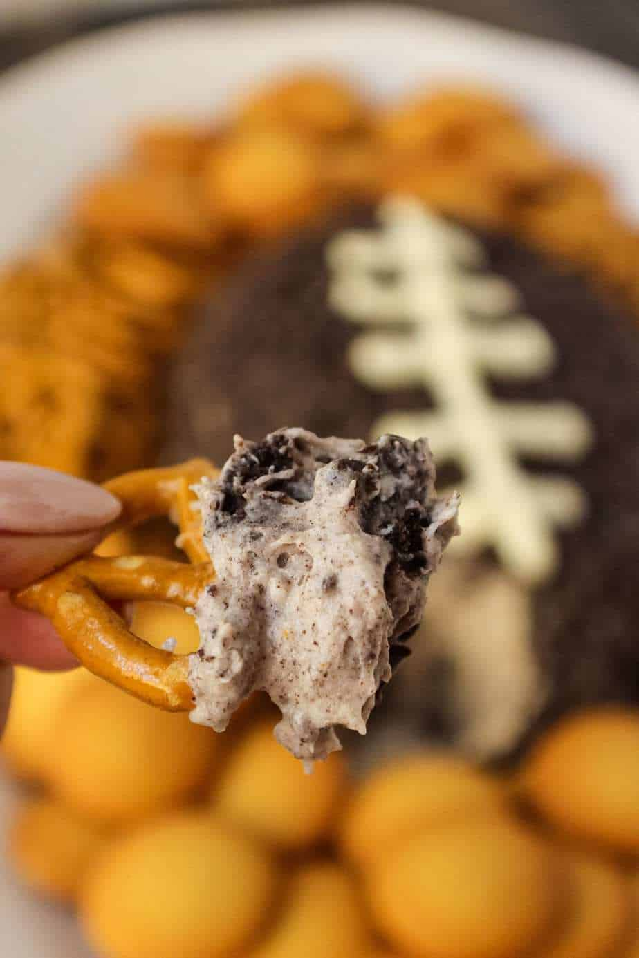 Cookies and cream cheese ball shaped and decorated to look like a football. sitting on a white serving platter with pretzels and vanilla wafer cookies around cheese ball in background. pretzel with cheese ball filling on in in forefront of shot