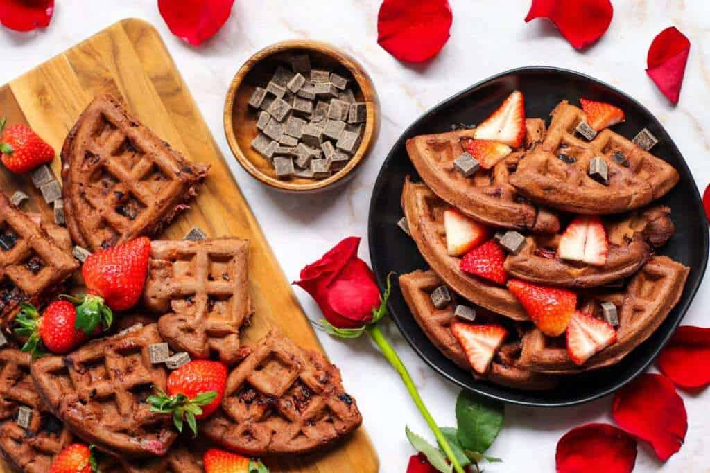 overhead shot of Double dark chocolate strawberry waffles topped with dark chocolate chunks and sliced strawberries. Rose and rose petals scattered in shot