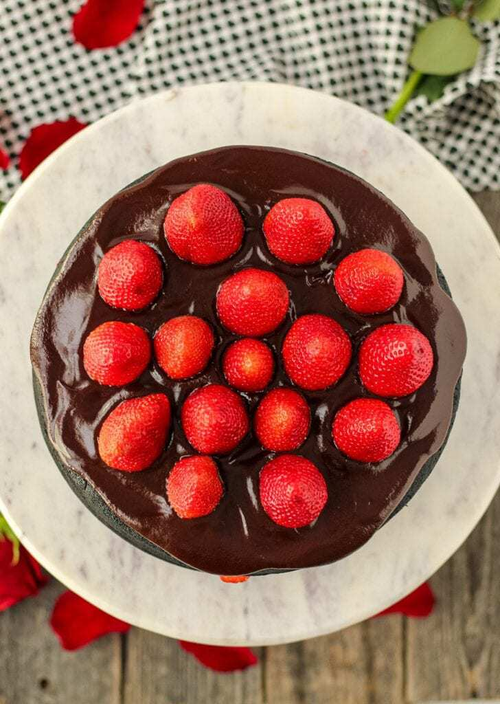 overhead shot of dark chocolate strawberry cake with chocolate ganache on top of marble and wood cake stand with strawberries on top of cake and cloth napkin in background/