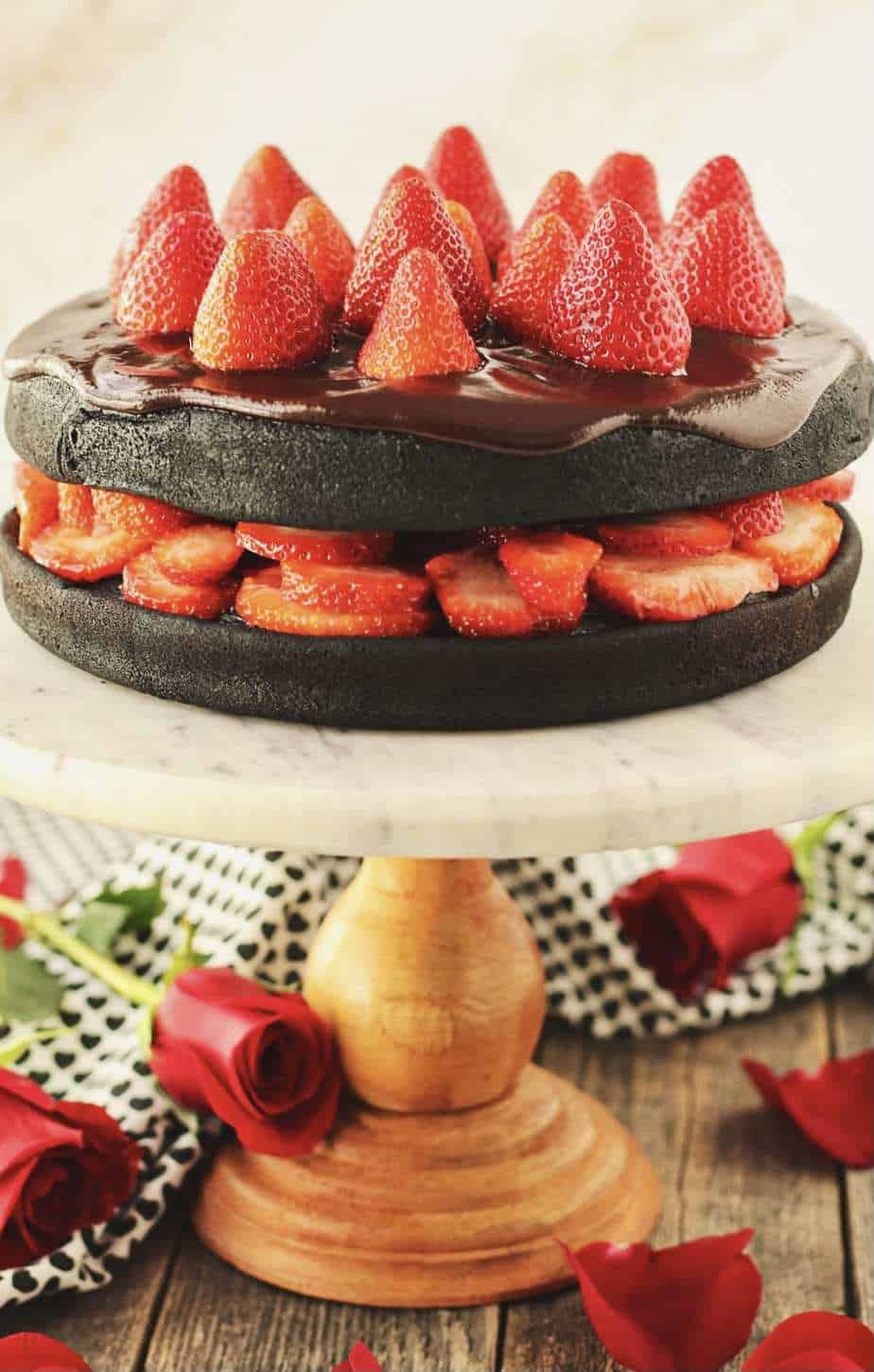 side angle shot of dark chocolate strawberry cake with chocolate ganache on top of marble and wood cake stand with strawberries arranged on top of cake and roses and cloth napkin in background.