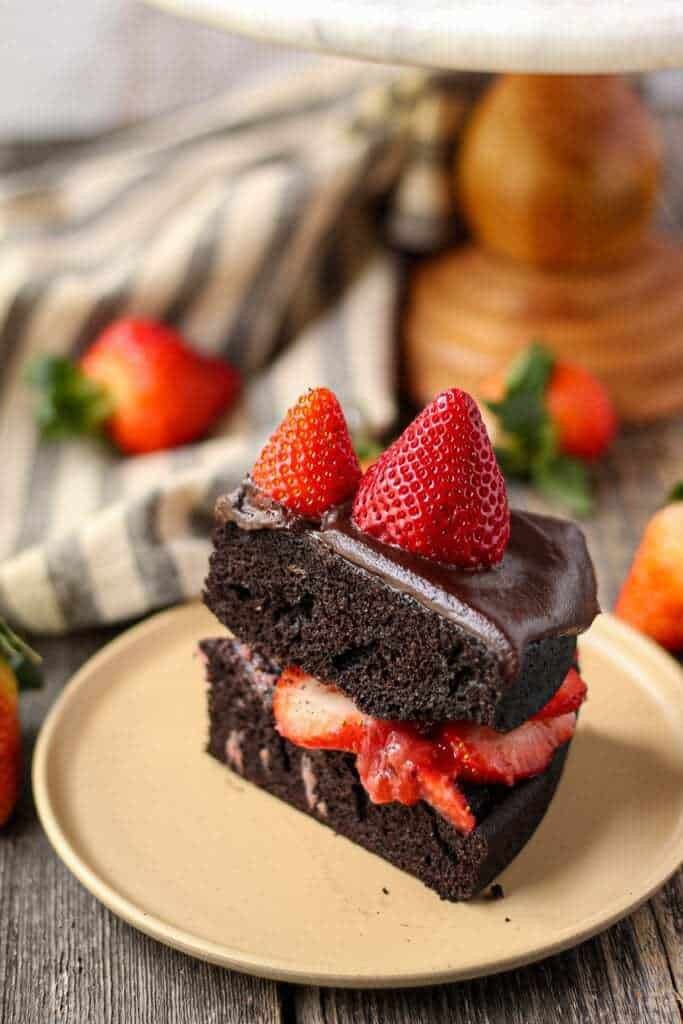 side angle shot of dark chocolate strawberry cake with chocolate ganache slice on tan colored plate with cake stand and strawberries in background.