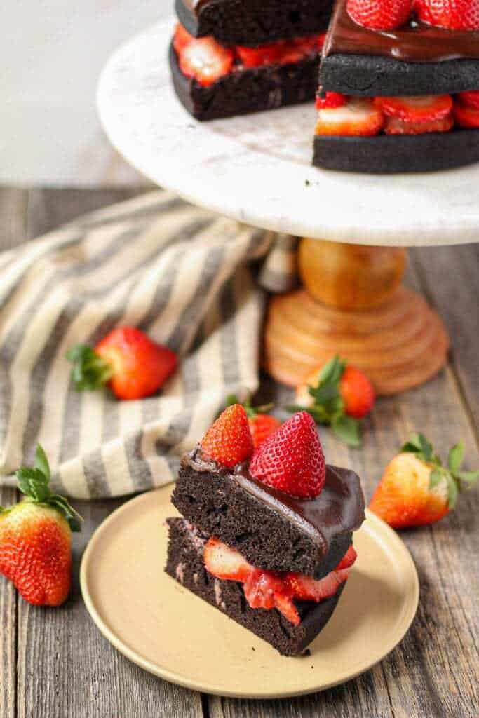 side angle shot of dark chocolate strawberry cake with chocolate ganache on top of marble and wood cake stand with a slice cut from the cake placed on small plate in bottom of shot.