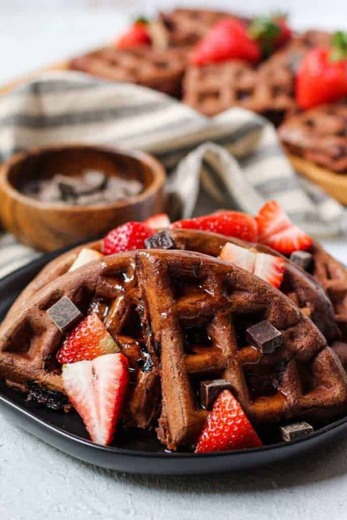 side angle shot of Double dark chocolate strawberry waffles topped with dark chocolate chunks, pancake syrup and sliced strawberries