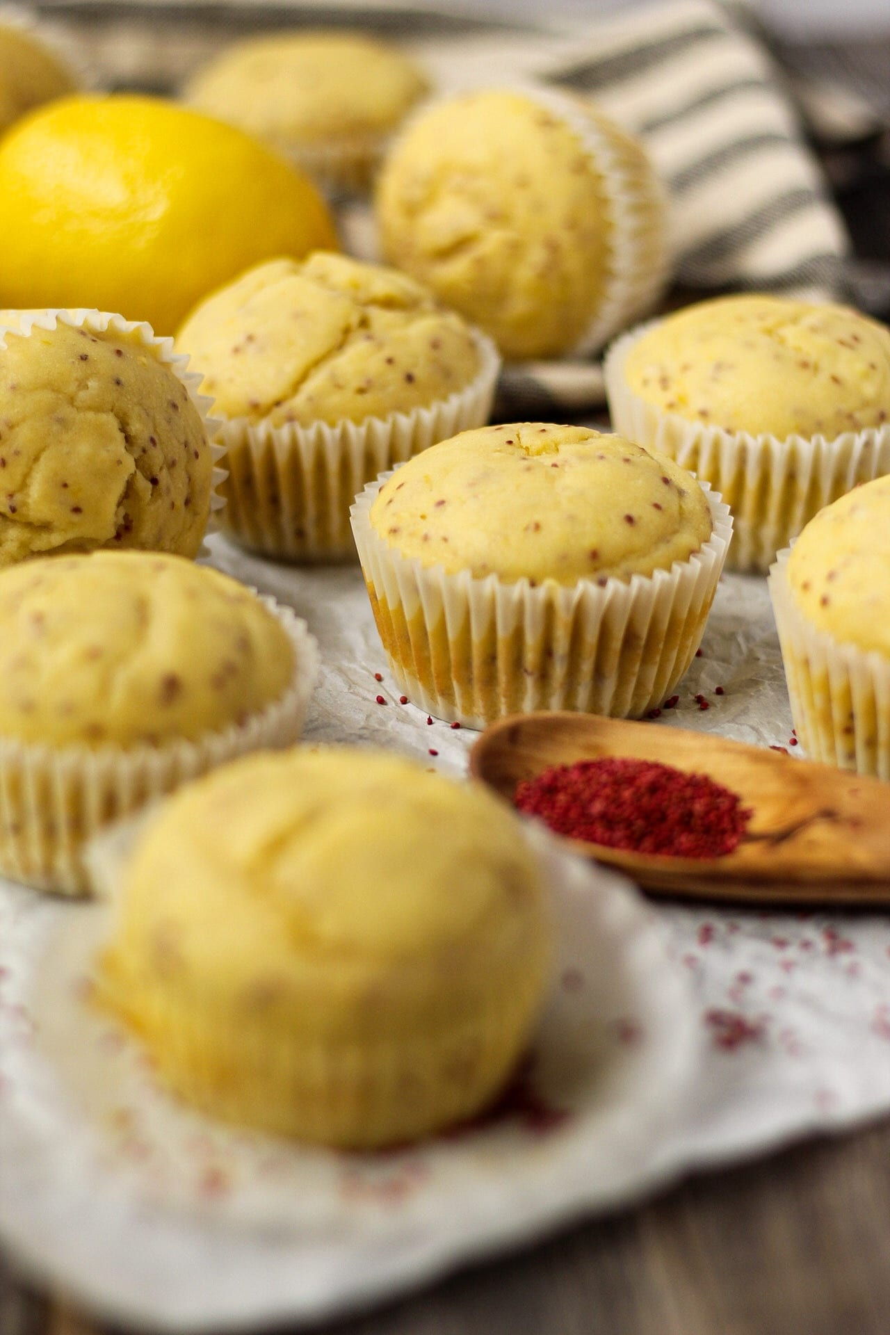 side angle shot of Lemon Cranberry Seed Cupcakes with Lemon Greek Yogurt Frosting on top parchment paper with cranberry seeds scattered on parchment and a wooden spoon filled with cranberry seeds in bottom right of shot. cloth napkin and whole lemon in background.