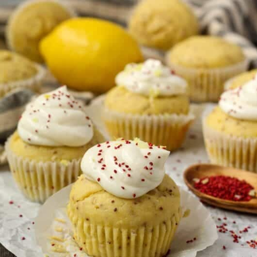 side angle shot of Lemon Cranberry Seed Cupcakes with Lemon Greek Yogurt Frosting on top parchment paper with cranberry seeds scattered on parchment and a wooden spoon filled with cranberry seeds in bottom right of shot. cloth napkin in background.