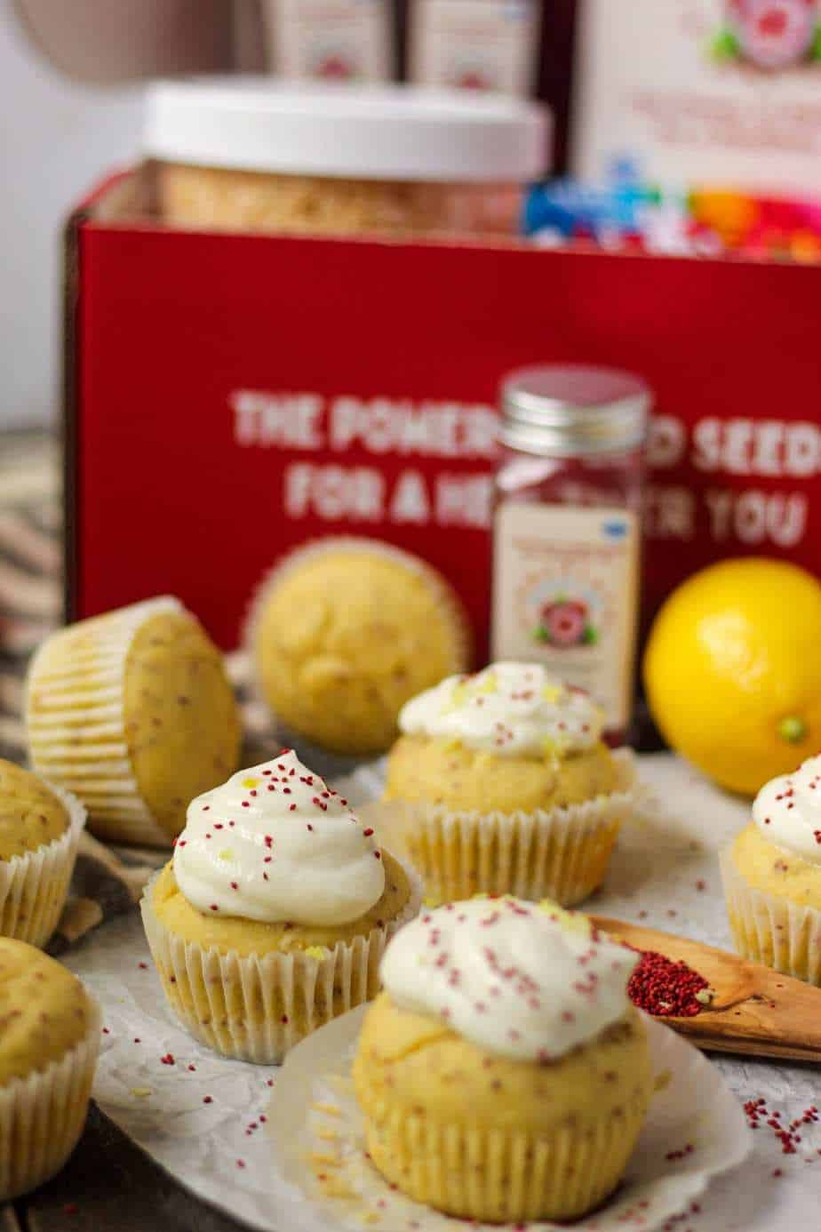 side angle shot of Lemon Cranberry Seed Cupcakes with Lemon Greek Yogurt Frosting on top parchment paper with cranberry seeds scattered on parchment and a wooden spoon filled with cranberry seeds in bottom right of shot. Cranberry seed container and box in background.
