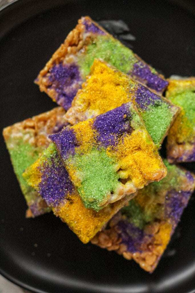 overhead shot of rice krispy treats made with marshmallows, butter, cinnamon and brown sugar topped with green, yellow and purple sanding sugar. treats are on a black plate.