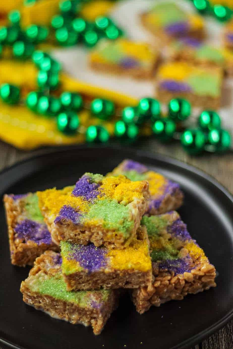 side shot of rice krispy treats made with marshmallows, butter, cinnamon and brown sugar topped with green, yellow and purple sanding sugar. treats are on a black plate and there are mardi gras beads in the background of the shot