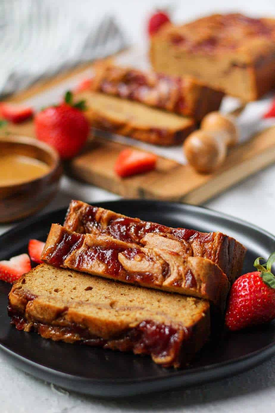 Peanut butter and jelly yogurt loaf cake on black plate with more cake on cutting board in background. cake has a strawberry jam swirl on top and is sliced to show texture.
