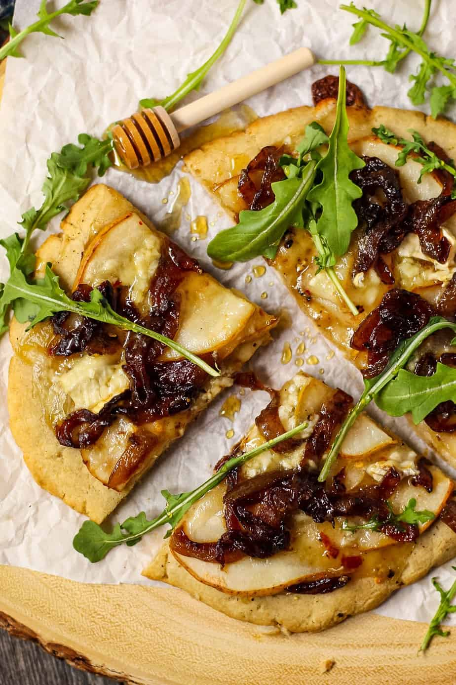 overhead shot of flatbread topped with sliced pears, caramelized onions and brie cheese. Garnished with arugula and honey. Flatbread is on top of parchment on a wooden serving board.