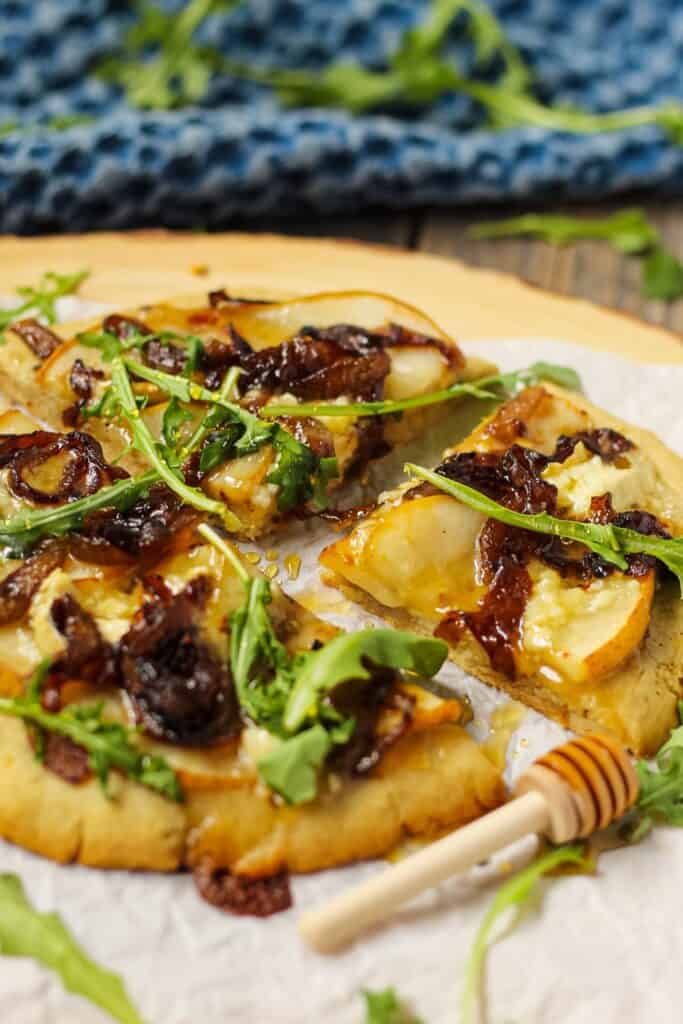 side shot of pear brie and caramelized onion topped flatbread on parchment on top of wooden serving board. garnished with honey drizzle and fresh arugula.