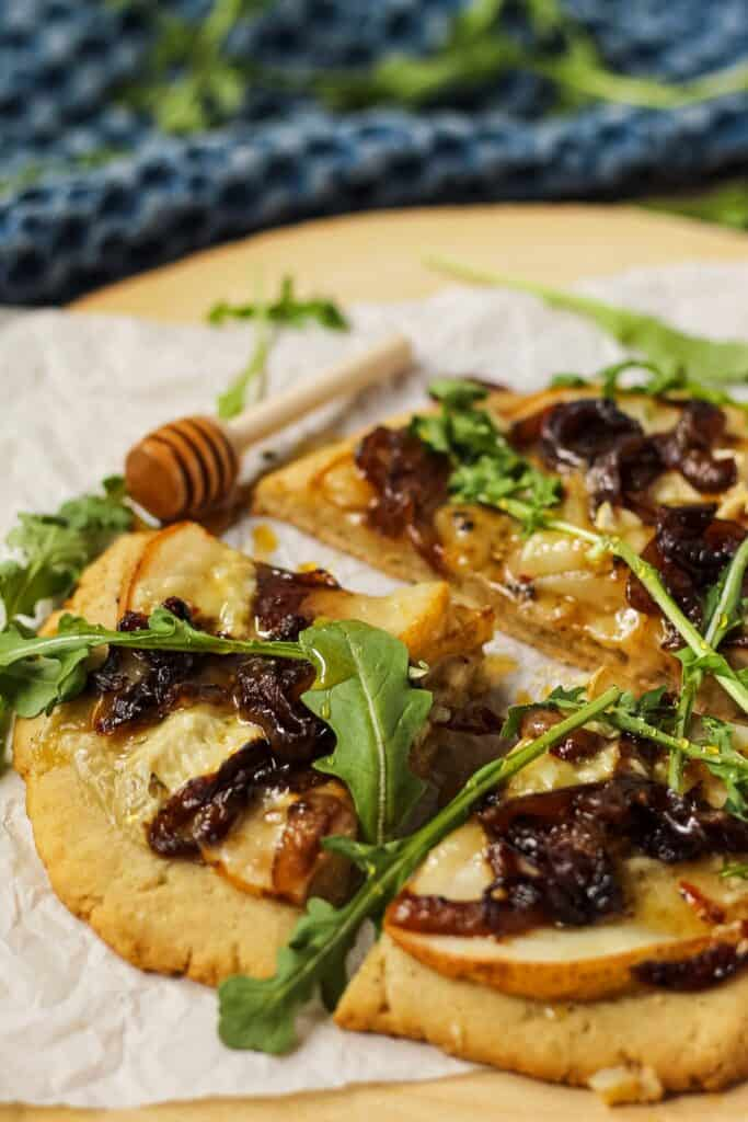 side angle shot of flatbread topped with sliced pears, caramelized onions and brie cheese. Garnished with arugula and honey. Flatbread is on top of parchment on a wooden serving board.