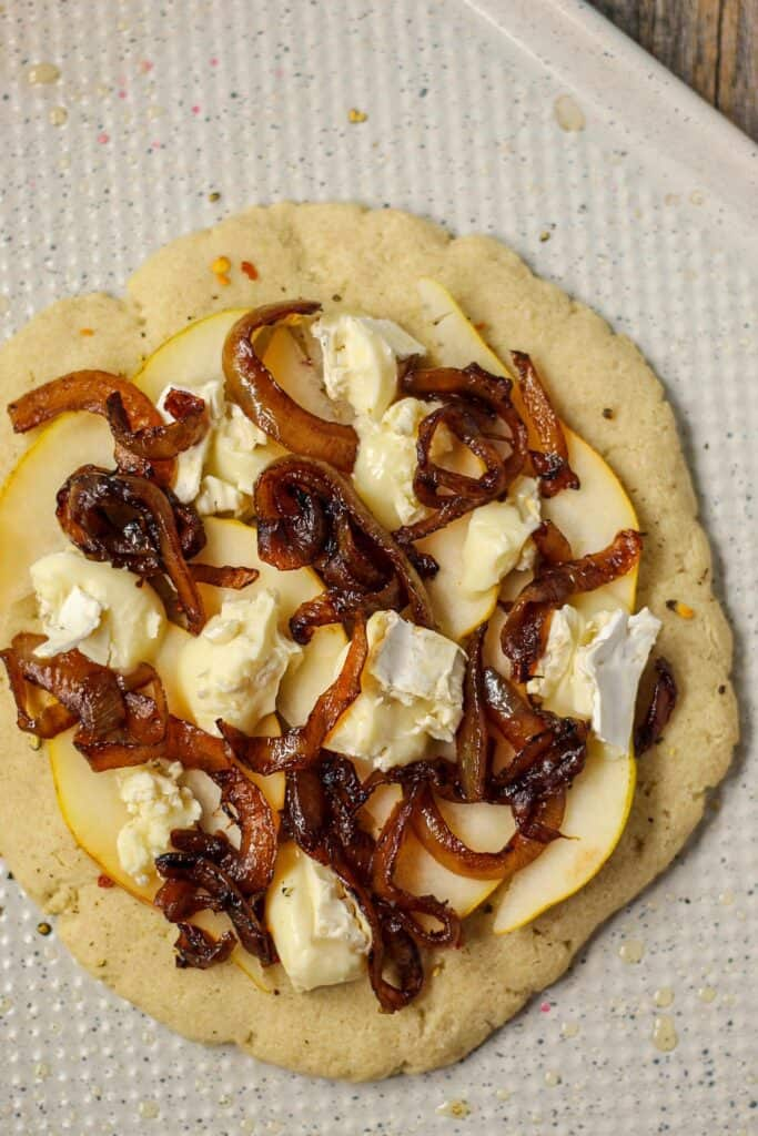 flatbread topped with pears, brie cheese and caramelized onion on a white baking sheet before being cooked