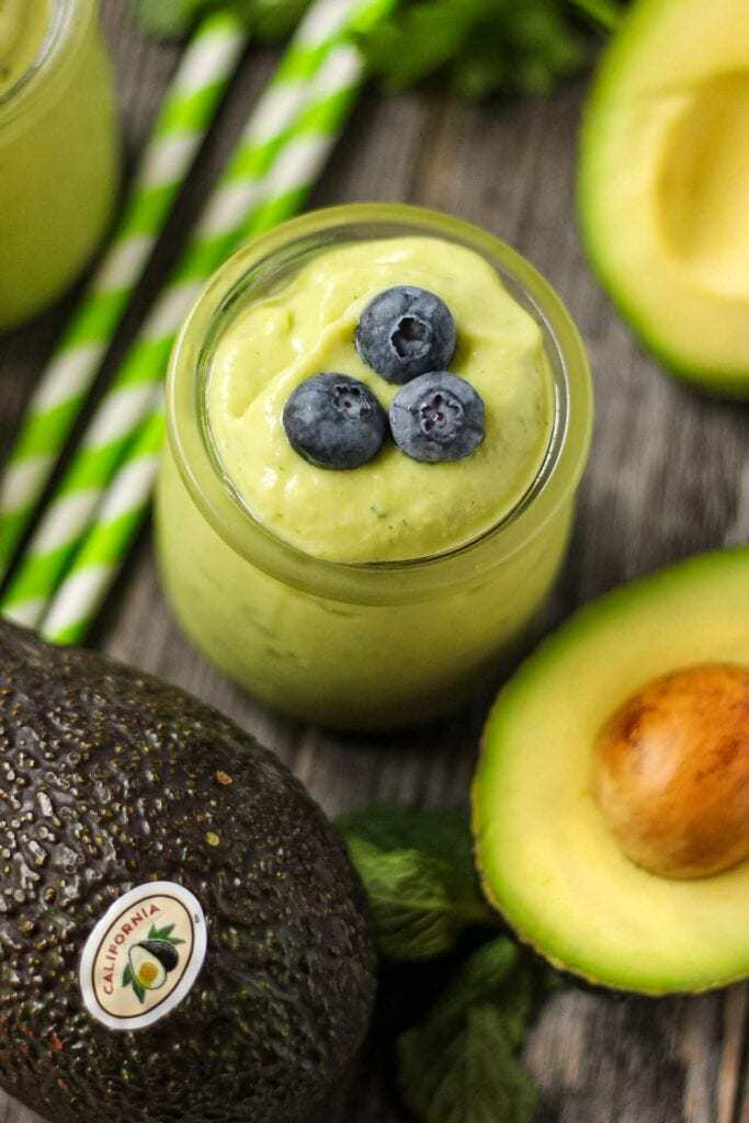 close up of tropical avocado smoothie in clear glass with fresh avocados in perimeter.