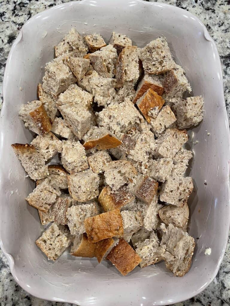 overhead shot of cubed whole grain bread in glass baking dish