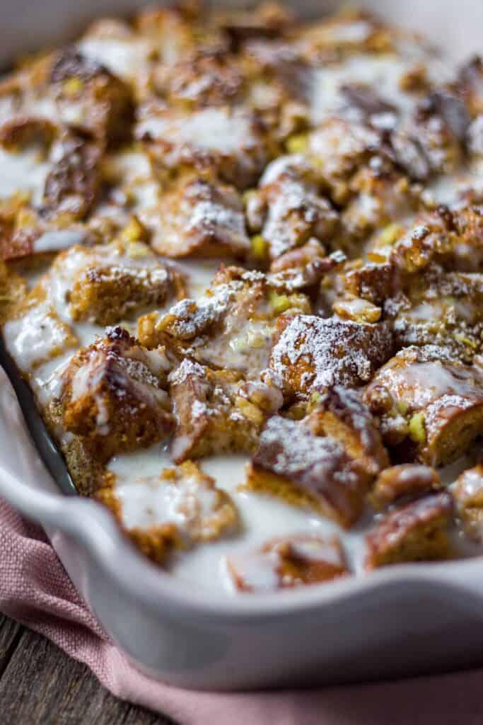 side shot of lemon bread pudding with lemon greek yogurt glaze in a terra cotta baking dish on wooden surface.